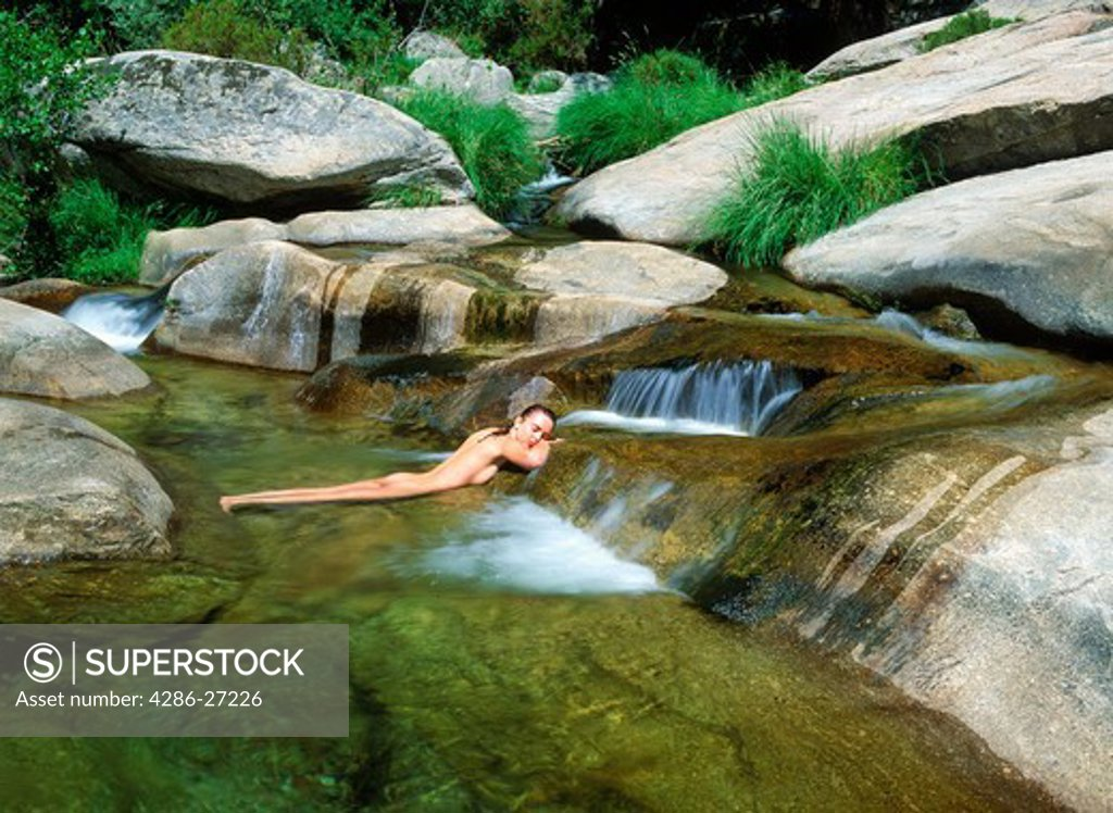Woman lying naked in mountain stream Stock Photo 4286