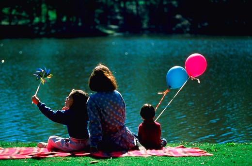 Mother and children sitting by lake, MR : Stock Photo