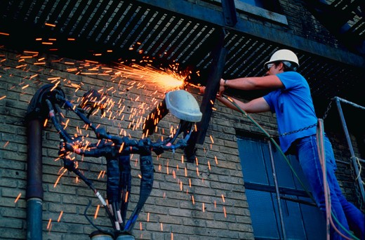 Worker uses acetylene torch : Stock Photo
