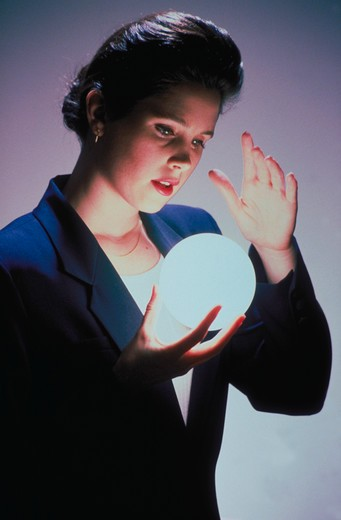 Stock Photo: 4286-16545 A business woman gazes into a glowing ball that she is holding as if to see the future.