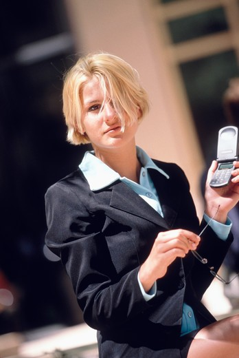 Stock Photo: 4286-16575 Portrait of a blonde female executive sitting outside holding her glasses and a cellular phone.