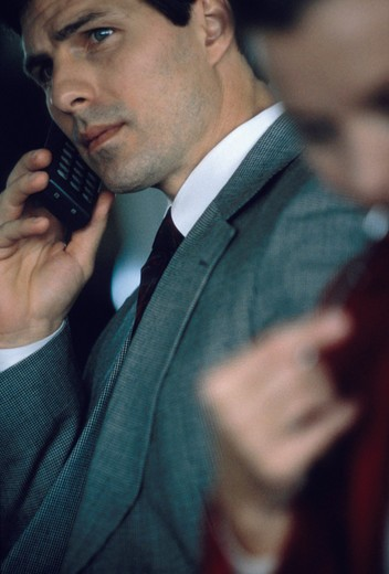 Stock Photo: 4286-16595 A businessman talks on a cellular phone.  There is a businesswoman in the foreground out of focus.