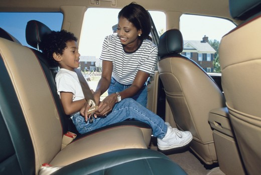 An African-American mother securing her son in a seat belt in the back seat of the auto. : Stock Photo
