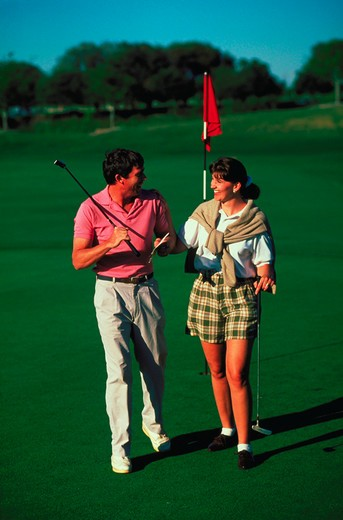 Stock Photo: 4286-16816 A smiling couple carrying golf putters walking across a putting green with the cup and flag in the background.