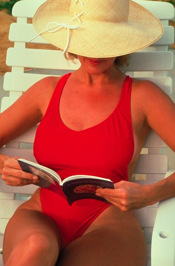 Stock Photo: 4286-16889 A woman wearing a red bathing suit and a wide brimmed hat relaxing on a lounge chair in the sun while reading a book.
