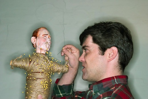 Young male artist sticking a pin into a voodoo doll.  MODEL RELEASED. : Stock Photo