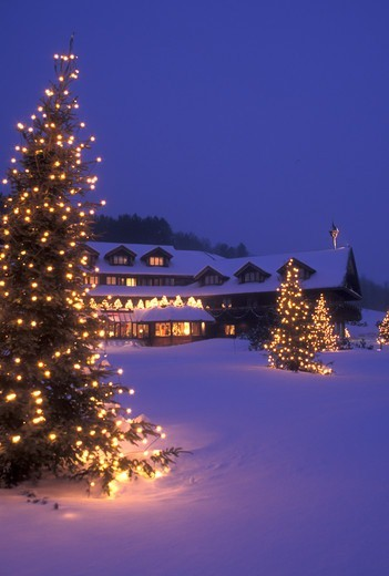 Stock Photo: 4286-19505 lodge, resort, inn, Trapp Family Lodge, Christmas, X-mas, Xmas, winter, trees, Vermont, The snow covered Trapp Family Lodge is decorated with lights in the evening for the Christmas holiday season in Stowe in Lamoille County in the state of Vermont. Evergreen trees with tiny white lights stand on the front lawn of the lodge.