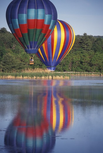 Stock Photo: 4286-19516 hot air balloon, Vermont, VT, Quechee, Two hot air balloons hover above the misty water at the Quechee Hot Air Balloon Festival.