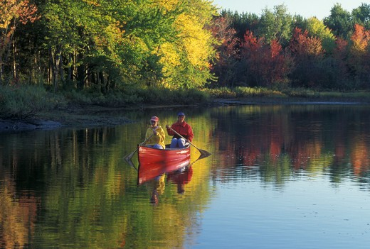 Stock Photo: 4286-19537 canoeing, canoe, Vermont, VT, Mother and daughter paddling a red canoe down Clyde River in Charleston in the fall.