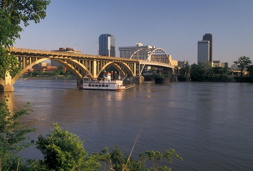 Stock Photo: 4286-19956 Little Rock, skyline, AR, Arkansas, A riverboat cruises under a bridge crossing the Arkansas River and a view of the downtown skyline of Little Rock.