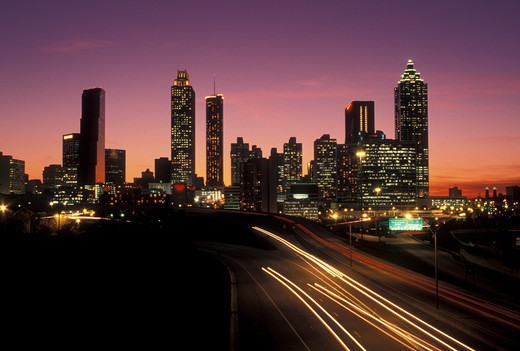 Stock Photo: 4286-20190 traffic, road, skyline, Atlanta, GA, Georgia, Traffic lights streak on Freedom Parkway at sunset and view of the skyline of downtown Atlanta.
