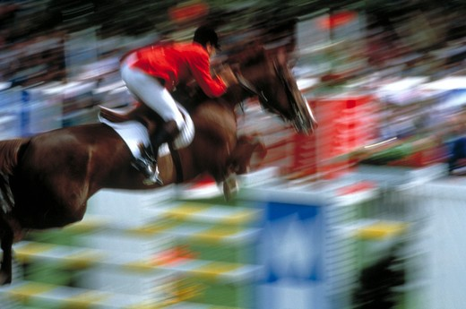 Horse and rider jumping, blurred : Stock Photo