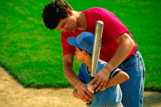 Stock Photo: 4286-21281 Dad/coach helps youth league player work on batting abilities.MR