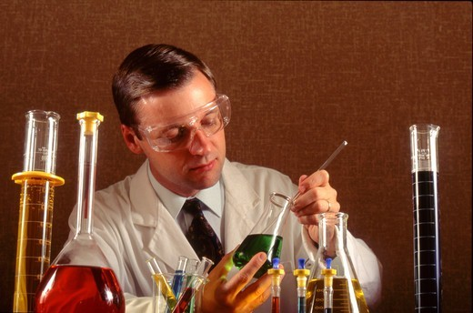 Chemist stirs solution in flask  : Stock Photo