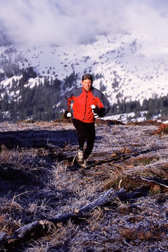 A man running in the back country in winter in the Sierra mountains of California.. : Stock Photo