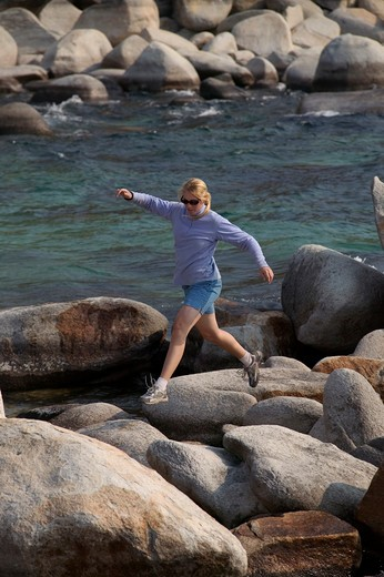 Stock Photo: 4286-21725 A woman running and rock hopping along the shore of Lake Tahoe, CA.