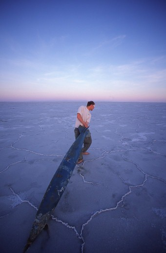 Stock Photo: 4286-21894 A man pretendsing to steal a fake bomb on the Bonneville Salt Flats in Utah.