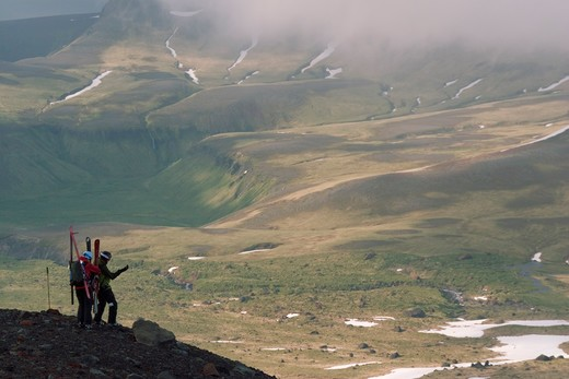 Stock Photo: 4286-22127 Two skiers climbing Mount Vsevidov in the Aleutian islands above green tundra.