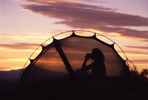 A silhouette of a woman in her tent drinking during a sunset at Smith Rock, OR. : Stock Photo