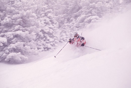 Stock Photo: 4286-22246 A blurry shot of a man skiing powder at Snowbird, UT.