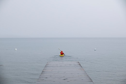 Stock Photo: 4286-22642 A man kayaking on Lake Tahoe in the fog in winter.