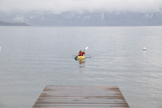 A man kayaking on Lake Tahoe in the fog in winter. : Stock Photo