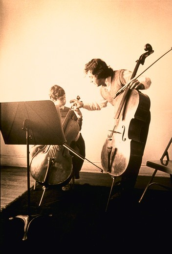 Stock Photo: 4286-23062 Hand colored image of music teacher with cello bending over to fix 12 yo male student's hand as he sits with his cello.