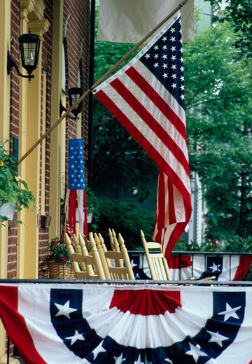 Stock Photo: 4286-23088 American flag and bunting hanging on the front porch of a house in Chautauqua, New York.