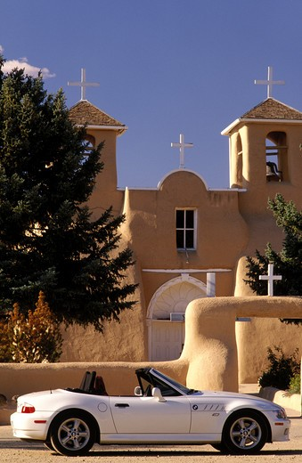 Stock Photo: 4286-23477 USA New Mexico Rancho de Taos Sports car BMW Z3 parked in front of Church of San Francis of Assisi established 1730