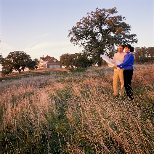 Middle-age couple stand in a field gazing into the sunset as they hold a set of blueprints. Nearby a large house is being built. : Stock Photo