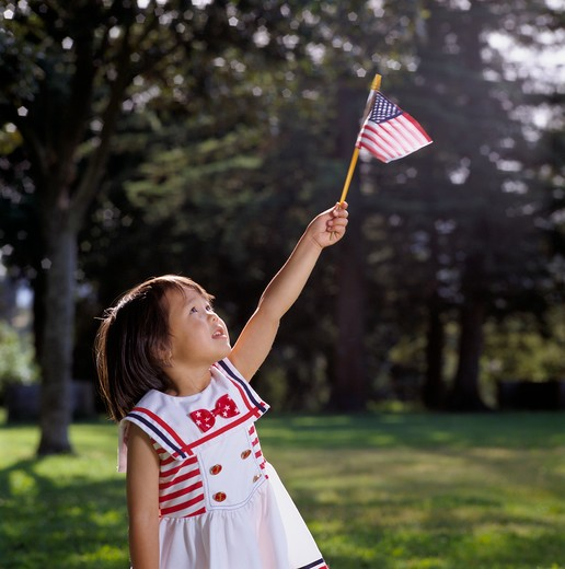 Stock Photo: 4286-24196 Young girl outdoors wearing a white dress with red bow holds a small U.S. flag aloft in her hand and looks skyward.