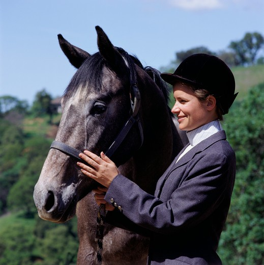 A smiling young woman in a formal gray riders outfit and black helmet strokes the face of her horse as she holds its bridle. : Stock Photo