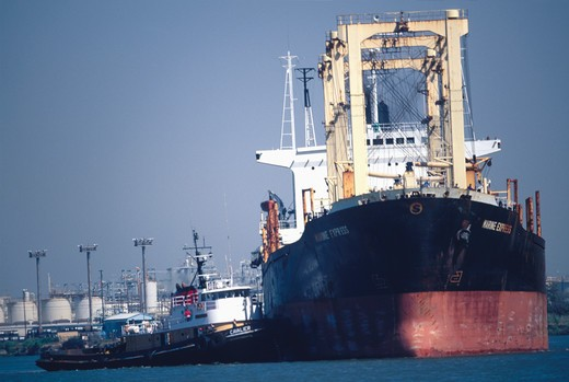 Stock Photo: 4286-24211 Tugboat nudges a sea-going freighter in the harbor of Pittsburg, California.