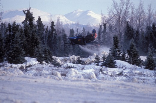 USA, Alaska, Anchorage, snowmobile races with snow capped peak : Stock Photo