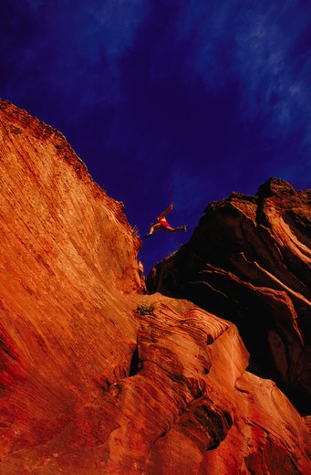 Stock Photo: 4286-24757 Man leaping across rock formations, Sterling Canyon, Arizona.