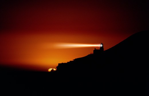 Stock Photo: 4286-24987 Light beams radiate from Point Conception lighthouse against orange sky just after sunset, California.