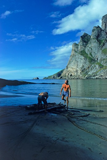 Two hikers building makeshift raft from driftwood in Lofoten Islands : Stock Photo