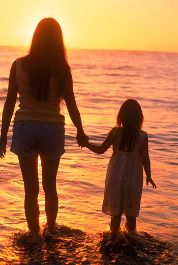 Mother and daughter holding hands on beach in sunset light : Stock Photo