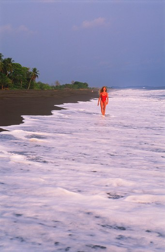 Stock Photo: 4286-27161 Woman on black lava shores of Playa Hermosa on Pacific Coast of Costa Rica