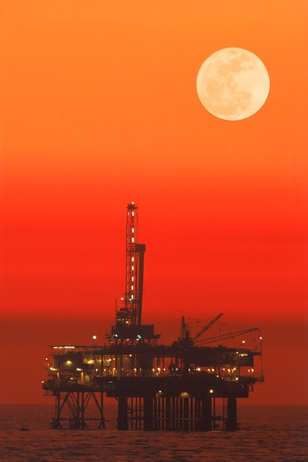 Offshore oil rig under full moon at Huntington Beach California : Stock Photo