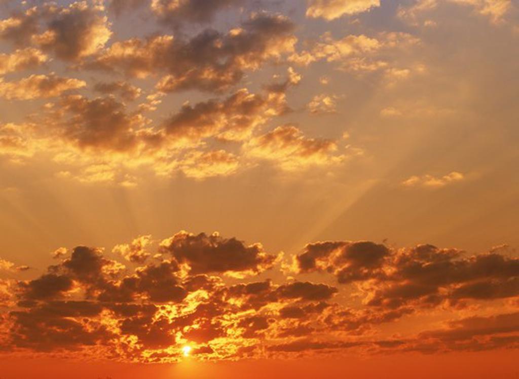 Sun rays bursting through cloudy skies : Stock Photo