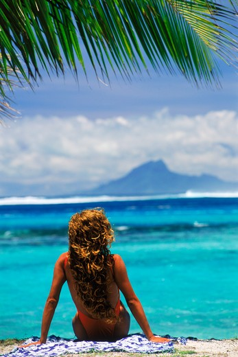 Stock Photo: 4286-27251 Woman sitting on Huahine Island beach with Raitea Island beyond in French Polynesia