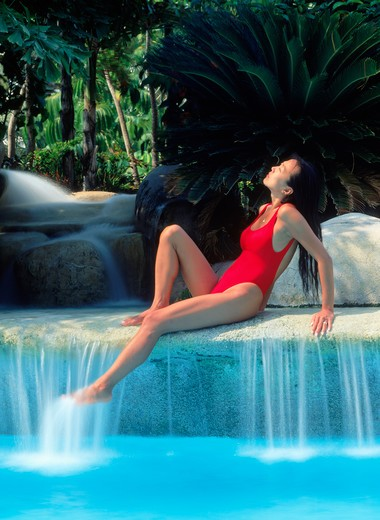 Woman at poolside waterfall in red bathing suit : Stock Photo