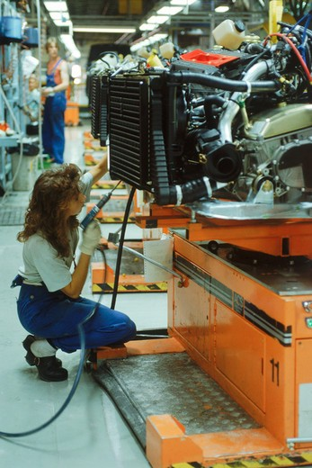 Stock Photo: 4286-27749 Woman working at Saab-Scania Plant with engines on automated trolleys in Sweden
