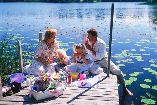 Family of four with picnic basket on lakeside pier during Swedish summer : Stock Photo