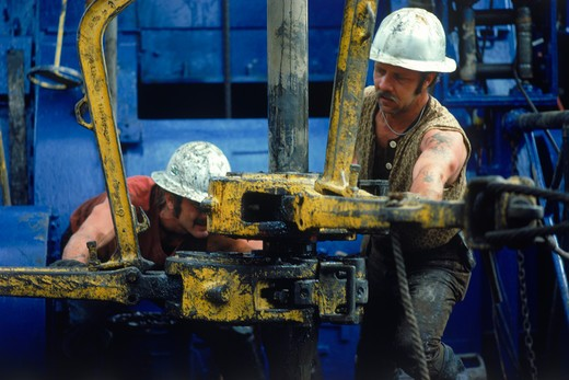 Stock Photo: 4286-28049 Men working on offshore oil rig coupling drill bits.