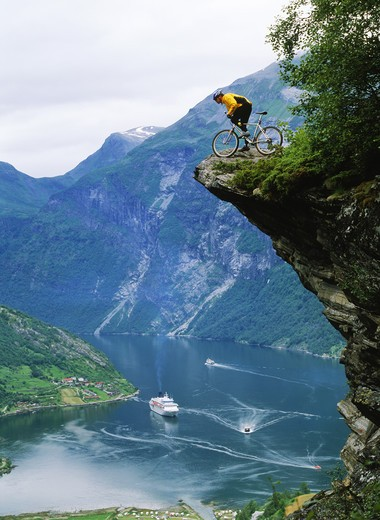 Stock Photo: 4286-28057 Mountain biker at Flydalsjuvet above Geiranger Fjord with cruise ship on Norwegian coast