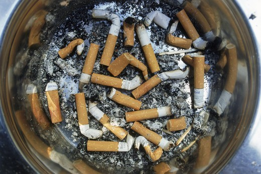 Ashtray filled with cigerette butts and ashes : Stock Photo