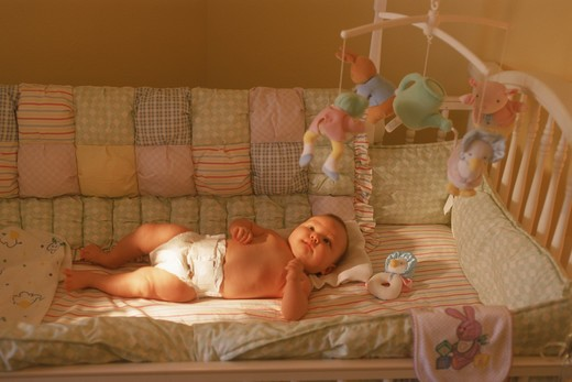 Stock Photo: 4286-28092 Baby in bassinet with toys hanging overhead