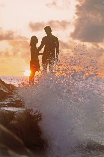 Stock Photo: 4286-28505 Couple standing on rocks at sunset with wave hitting shore in Seychelle Islands